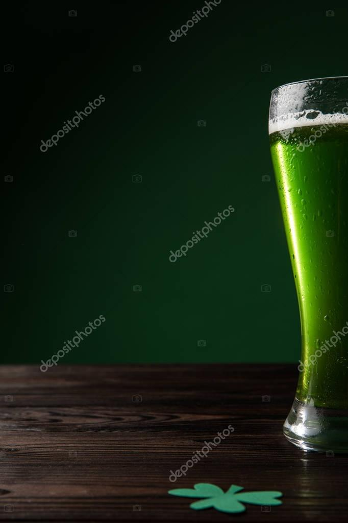 glass of green beer with shamrock on table, st patricks day concept