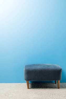 soft hassock standing on carpet in front of blue wall