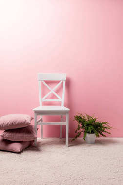 chair with pillows and fern pot in front of pink wall
