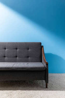 cozy grey couch in front of blue wall
