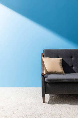 pillow lying on cozy couch in front of blue wall