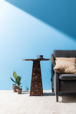 coffee table near cozy couch in front of blue wall
