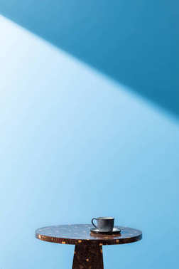 cup on coffee table in front of blue wall