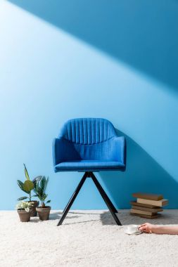 comfy blue armchair with person holding cup of coffee on floor in front of blue wall