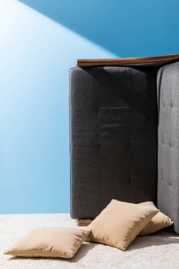 couch with pillows flipped on side in front of blue wall