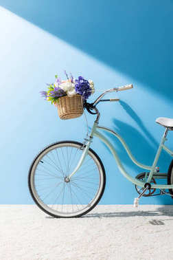 Bicycle with beautiful flowers in basket in front of blue wall stock vector