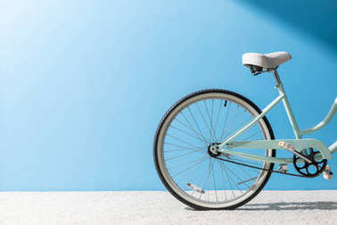 back wheel of bicycle standing on carpet in front of blue wall