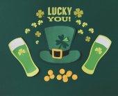 plochý ležel s brýlemi piva, mince, zelený klobouk, shamrocks a štěstí si nápisy na zelené pozadí