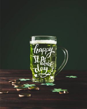 close up view of glass of beer on wooden tabletop and happy st patricks day lettering