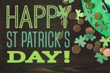 flat lay with green hat, coins and shamrocks on wooden surface with happy st patricks day lettering