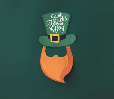 close up view of papercraft green hat and beard with saint patricks day lettering on green background