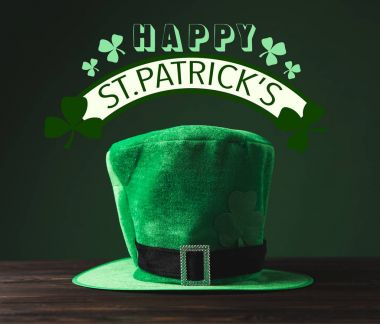 close up view of green hat on wooden surface and happy st patricks lettering