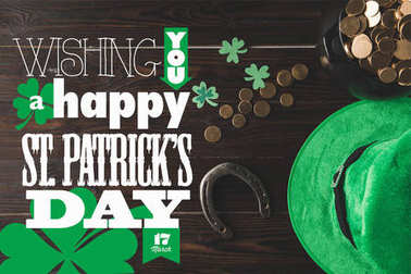 flat lay with horseshoe, hat and pot of gold on wooden tabletop with wishing you a happy st patricks day lettering