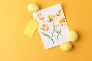 top view of yellow painted easter eggs with postcard on yellow