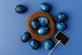 top view of blue painted easter eggs in decorative nest on blue surface