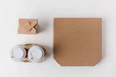 top view of pizza box and disposable coffee cups with noodles box on white