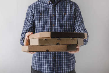 cropped image of male courier holding pizza boxes isolated on grey
