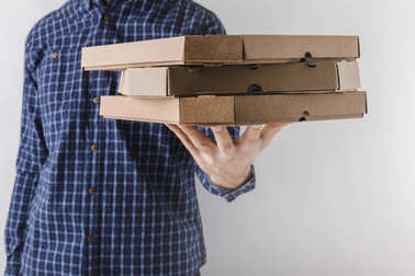 cropped image of courier holding pizza boxes on one hand isolated on white