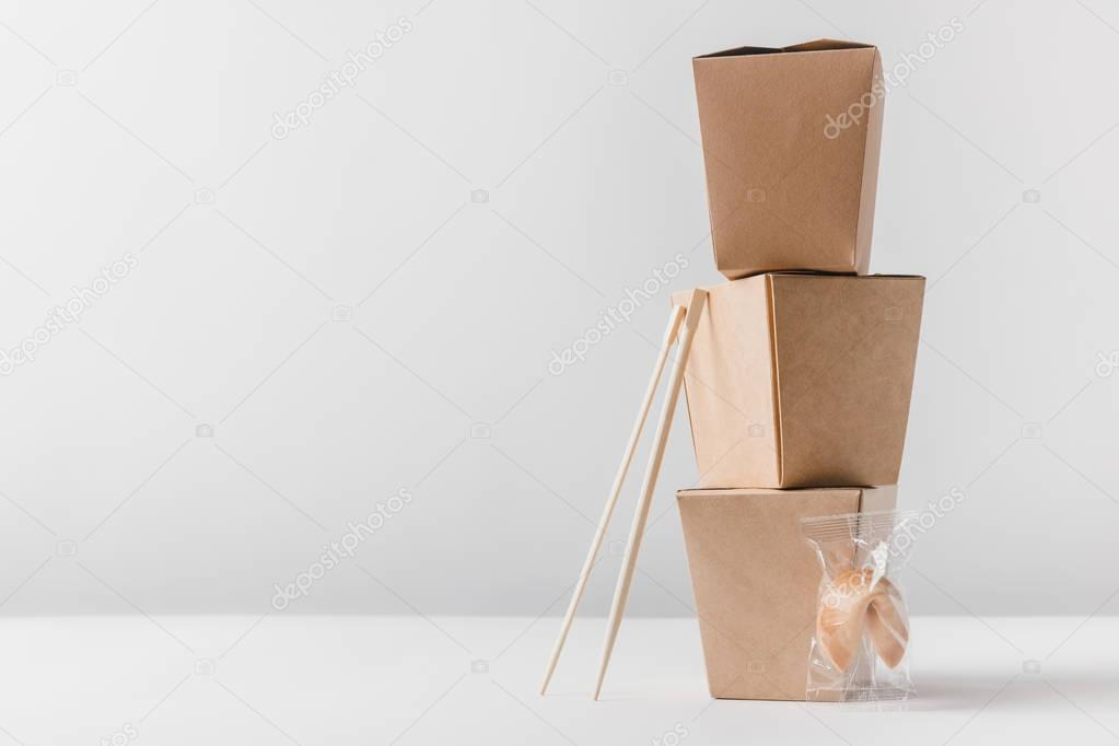 noodles boxes with chopsticks and chinese fortune cookie on tabletop