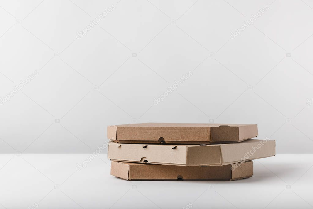 three pizza boxes on white tabletop