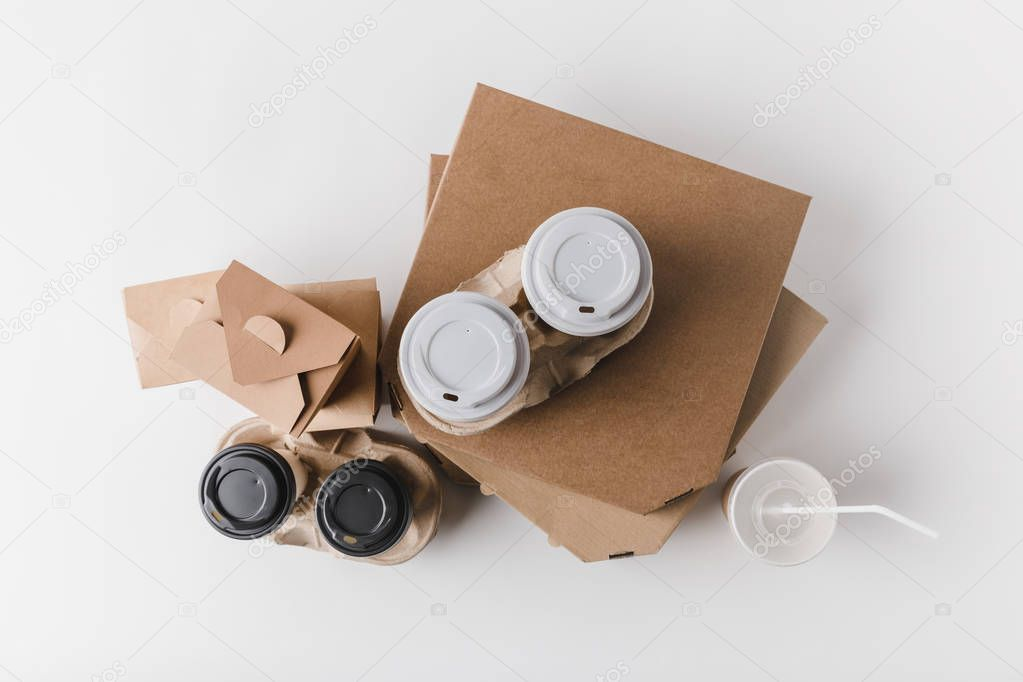 top view of pizza boxes and coffee to go with food containers on tabletop