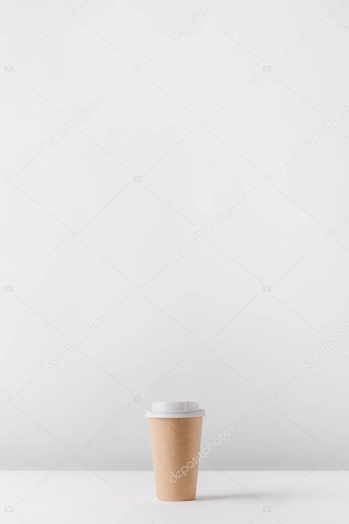one disposable coffee cup on white table