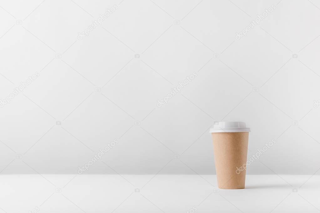 disposable coffee cup on white surface