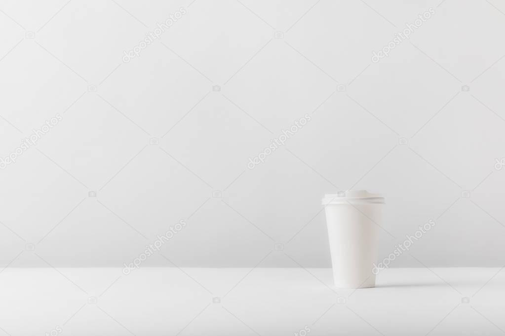 white disposable coffee cup on white tabletop