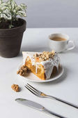 Tazza di caffè, torta e posate con pianta conservata in vaso sulla tabella
