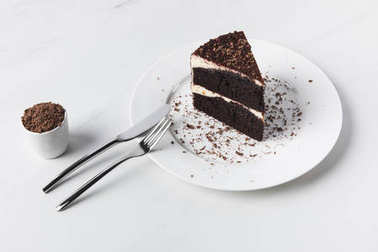 Grated chocolate in bowl, cutlery and cake on plate