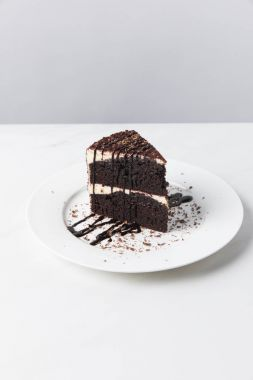 Front view of chocolate cake with glaze on plate placed on white surface