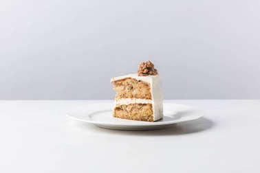 Plate with cake and walnut on top on white surface