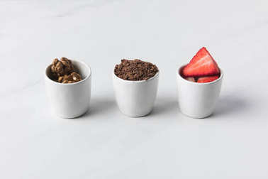 Closeup view of three bowls with walnuts, grated chocolate and strawberries on gray