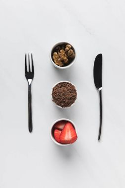 Bowls with walnuts, grated chocolate and strawberries between fork and knife, table appointments conception