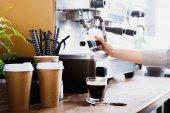 Nahaufnahme des Barista beim Zubereiten von Kaffee auf einer modernen Espressomaschine