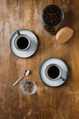 Two cups of black coffee and coffee beans in jar on wooden table