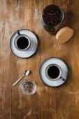 Dva šálky černé kávy a kávových zrn v jar na dřevěný stůl