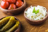 Photo close-up view of delicious pickled vegetables in bowls on wooden tabletop