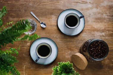 Morning black coffee in cups on table with plants in coffee shop