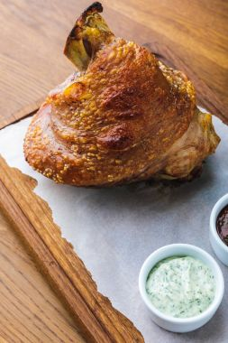 close-up view of tasty roasted pork knuckle with sauces on wooden board