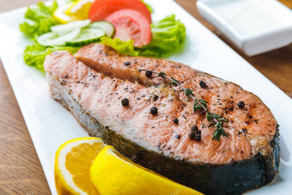 close-up view of gourmet roasted salmon with lemon slices and vegetable salad