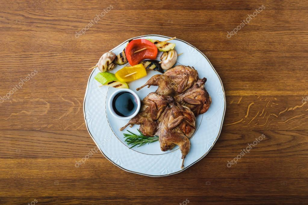 top view of roasted chickens with grilled vegetables and sauce on plate