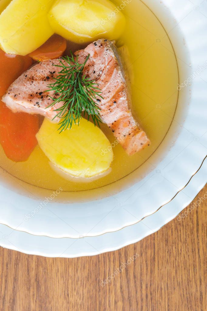 top view of delicious healthy salmon soup on wooden tabletop