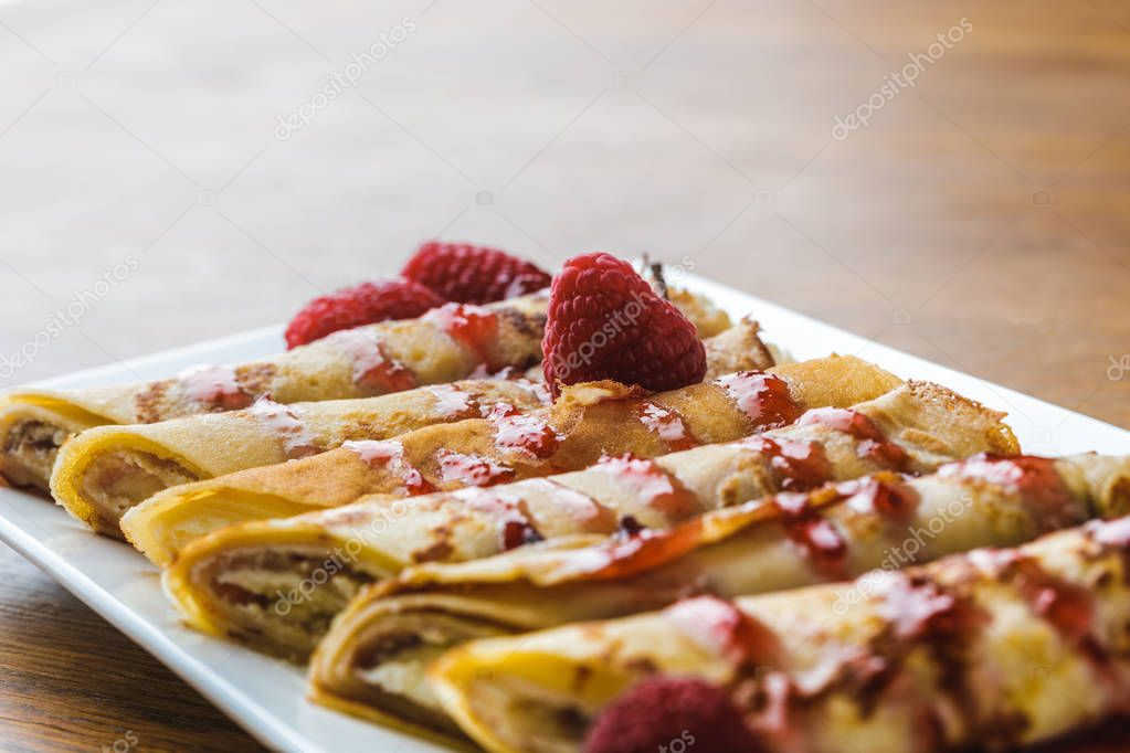 close-up view of sweet rolled pancakes with raspberries