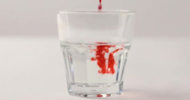 Pouring red syrup in glass with water on white background with reverse footage