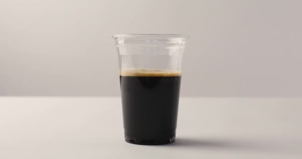 Pouring milk from jug in disposable cup with black coffee on white background