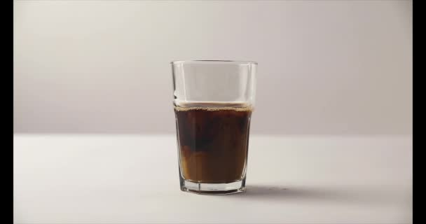 Slow motion of pouring milk in Old Fashioned glass with coffee on white background