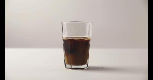 Rallentatore di versando il latte nel bicchiere Old Fashioned con caffè su priorità bassa bianca