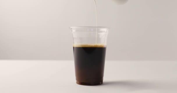 Nalil mléko z nádobky v plastový kelímek s kávou na bílém pozadí