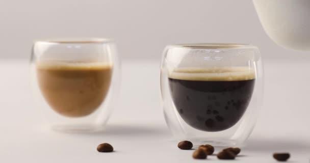 Nalil mléko z nádobky v jednom ze dvou šálků kávy na bílém pozadí s kávová zrna